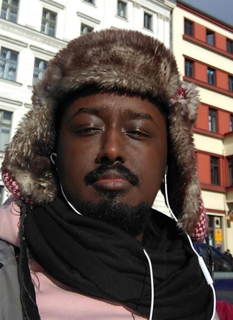 Axmed Maxamed is a Somali man wearing a fur deer stalker hat, black scarf and pink hoodie