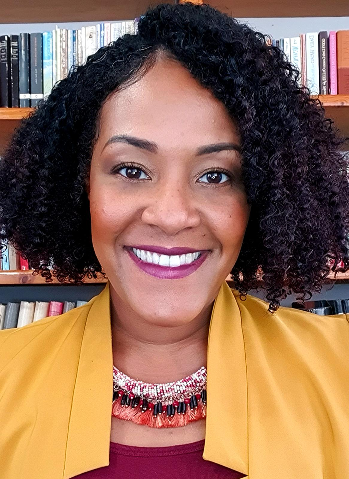Solange Ludmila Duncan, MP in Sint Maarten. She has mid-length curls and wears a yellow jacket, maroon top and lipstick